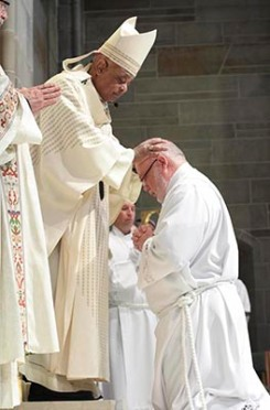 Photo By Michael Alexander  Archbishop Wilton D. Gregory lays hands upon diaconate candidate William Donohue of Prince of Peace Church, Flowery Branch.